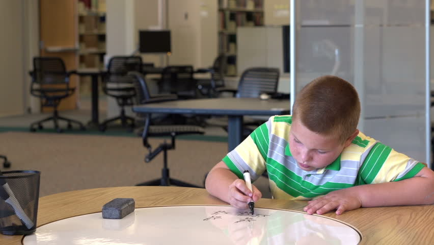 Young boy solving math problem looks up and smiles | Shutterstock HD Video #4412519