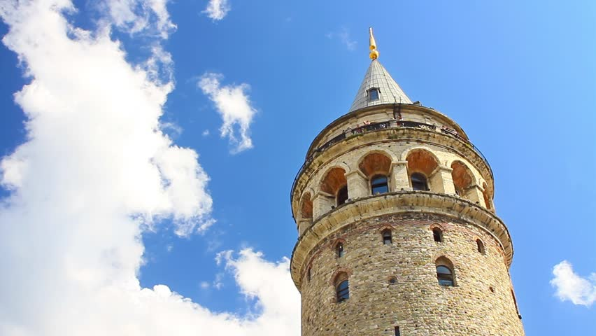 Galata Tower against fast white clouds. Timelapse
