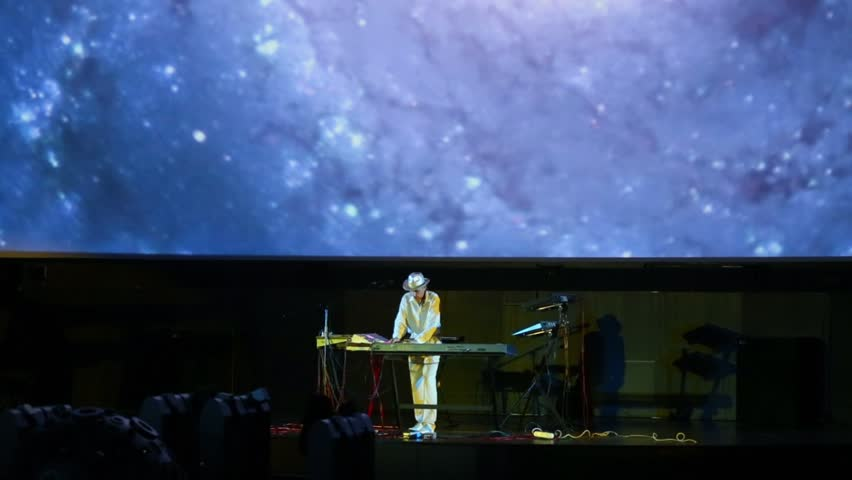 MOSCOW - JUN 15: Andrey Klimkovsky plays on music equipment near video screen during concert program Music of heavenly spheres in Big star hall of Moscow planetarium on 15 Jun 2012 in Moscow, Russia.