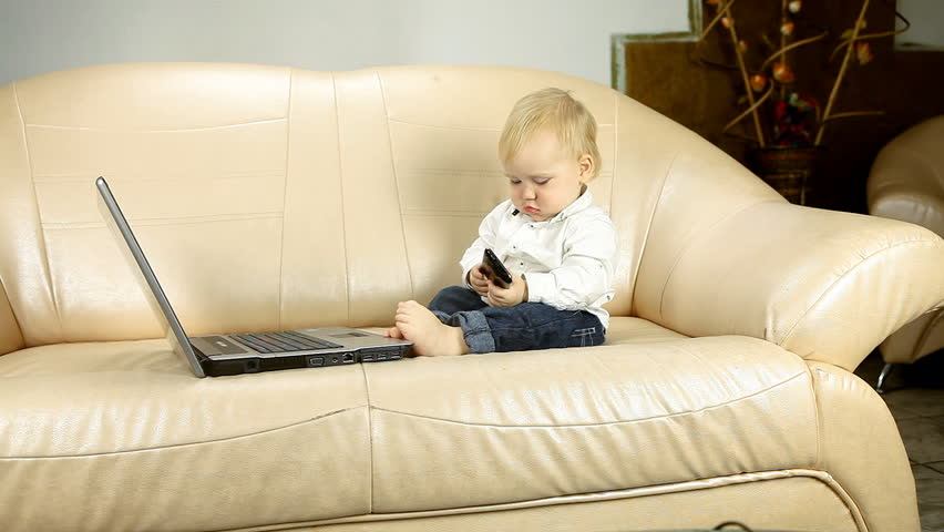 Child sitting on sofa and looks in laptop