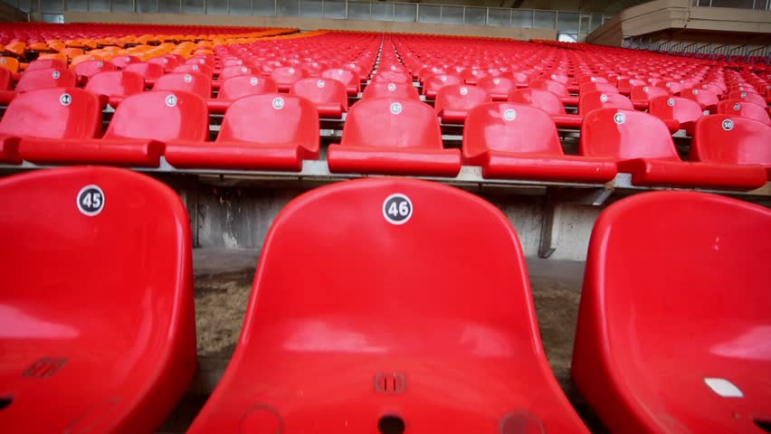 Rows of red and orange plastic seats at low price zone on stadium tribune