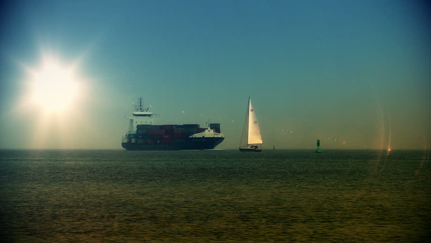 Cargo ship meets boat at sunset