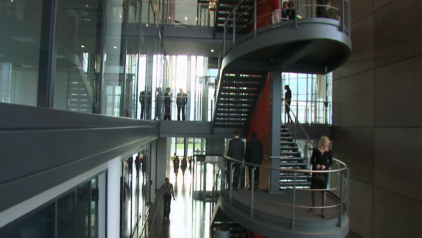 Following several business people as they enter a modern office building and through the reception area. Multiple staff members and managers walk through the lobby. High quality HD video footage