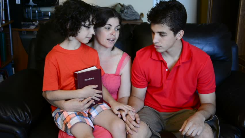 Hispanic family having a daily devotional at home. Single mother and her sons praying and studying the Bible