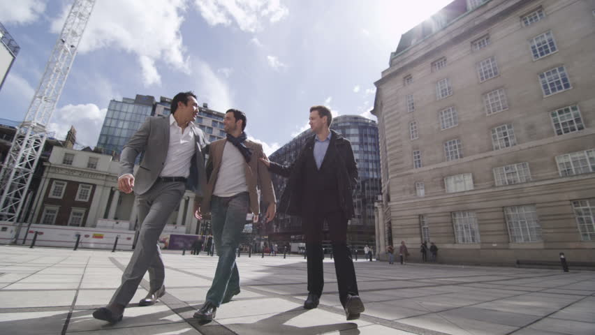 Young attractive male friends enjoying time together outdoors. Could have been to University together or are colleagues in a new business. Smart casual fashion, successful and trend conscious. - HD stock footage clip