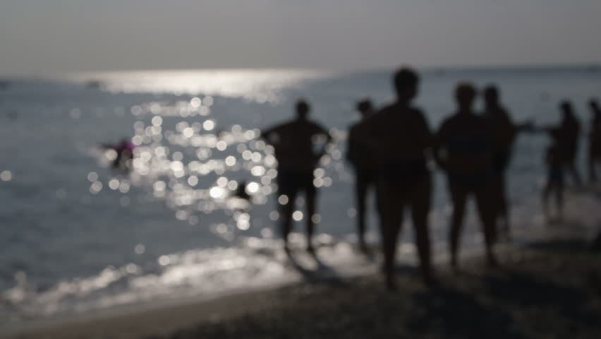 People Silhouettes on Summer Beach Out of Focus