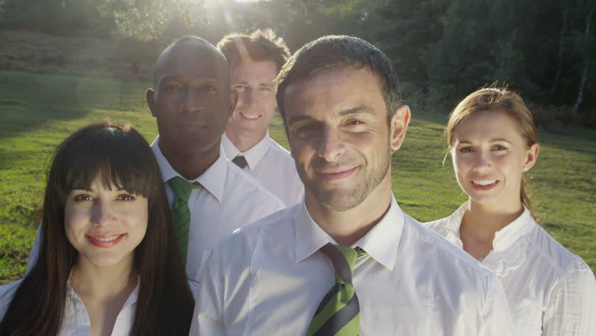 Business team look into camera outside. Corporate businessmen and businesswomen surrounded by grass.