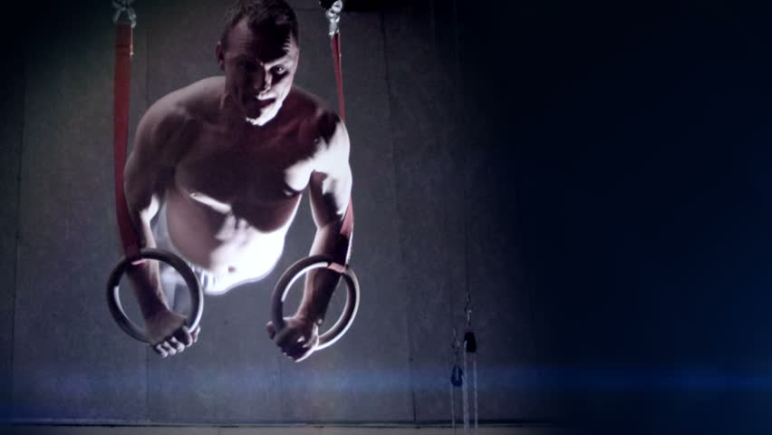 Male gymnast performing routine on gymnastic rings. Olympics sport in contemporary setting. Slow motion Shot on RED Epic at 240FPS