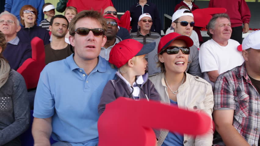 Boy with family in crowd of sports spectators. Could be a stadium crowd at the olympics, tennis tournament, American football, soccer match or baseball. People young and old cheering and smiling. - HD stock video clip