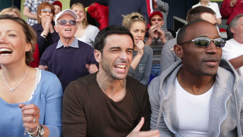 Enthusiastic crowd of spectators watching a sports game or football match and reacting  - HD stock video clip
