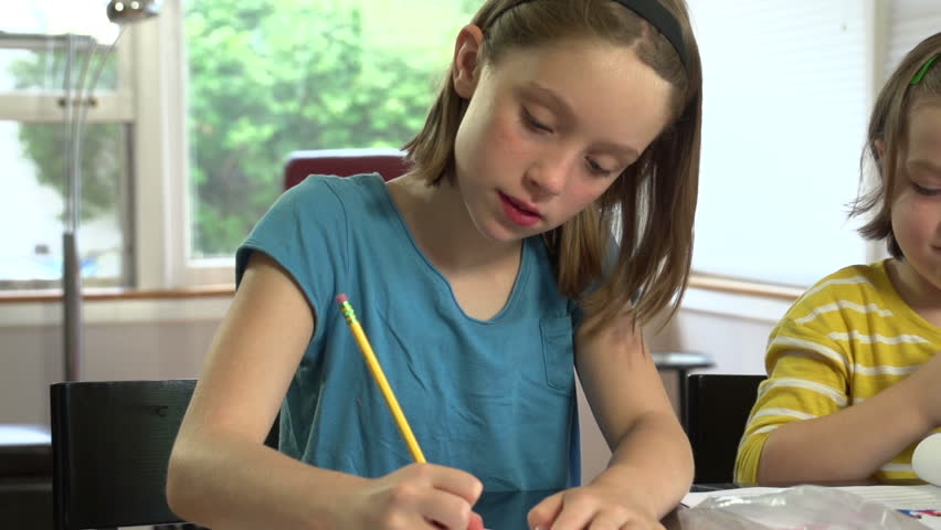 Sisters working on homework at the table | Shutterstock HD Video #4541372