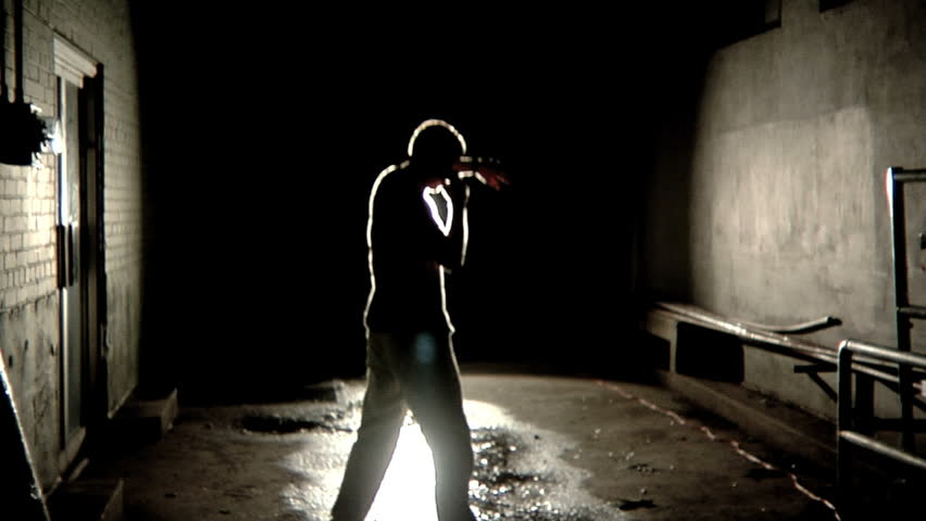 Bright light on man standing in alley
