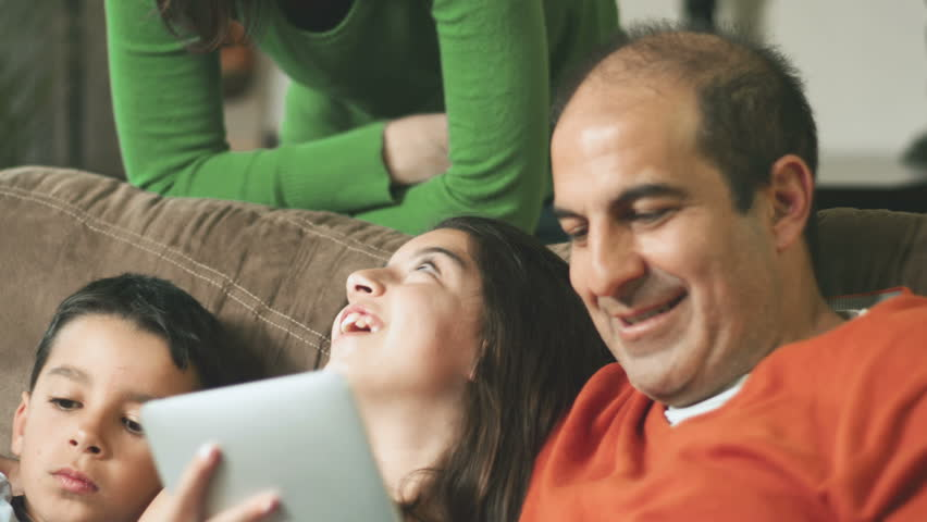 An adorable family sit together and play with a laptop and digital tablet. Close up shot