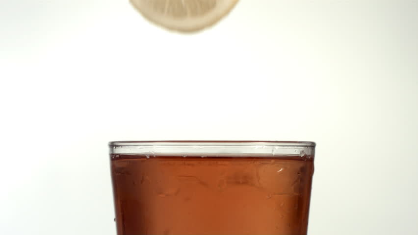 Lemon slice splashing into iced tea, slow motion