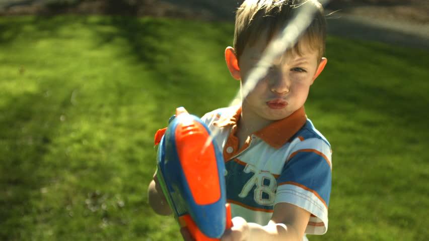 Young boy spraying squirt gun at camera   Shutterstock HD Video #4557608