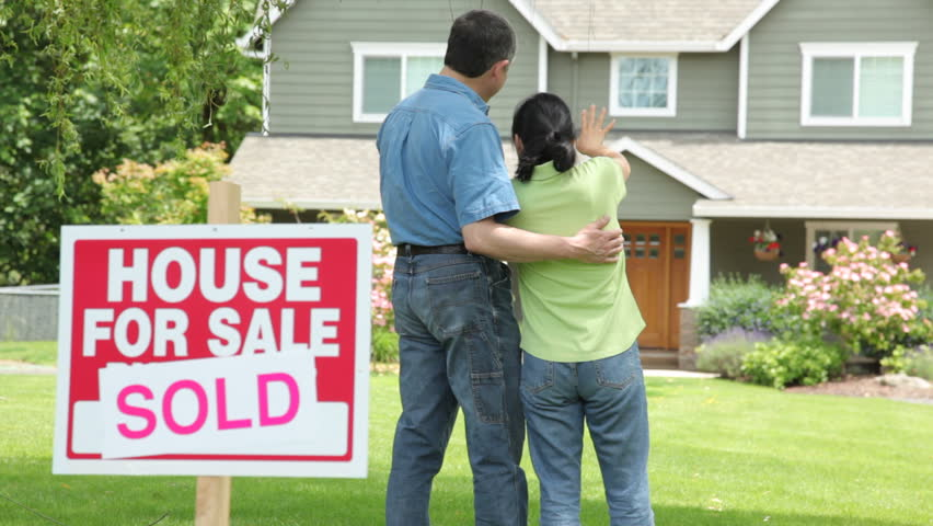 Couple look at new home, SOLD sign in foreground