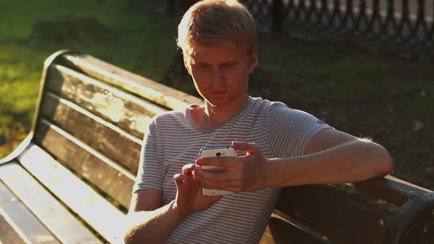 Young blond adult man writing sms message in park bench sitting