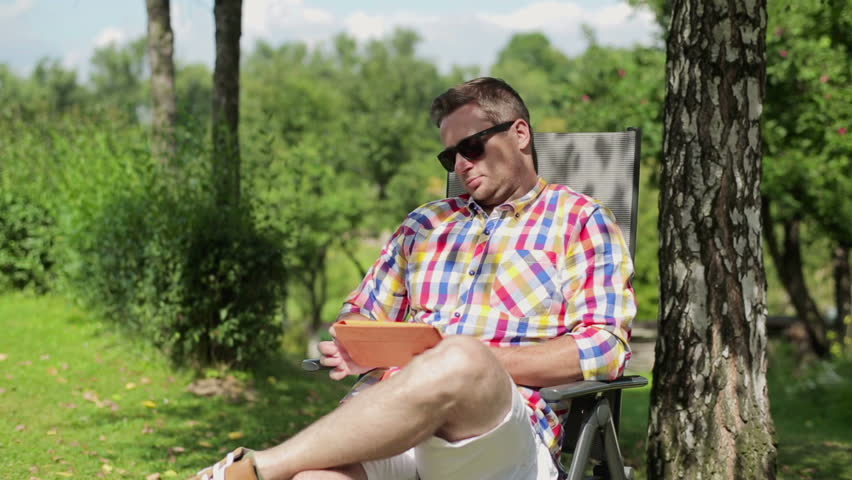 Man with tablet relaxing in the garden
