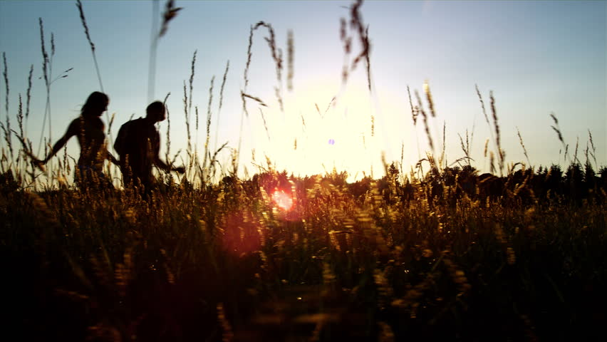 A silhouetted couple run, twirl and kiss in a wide open golden field at sunset