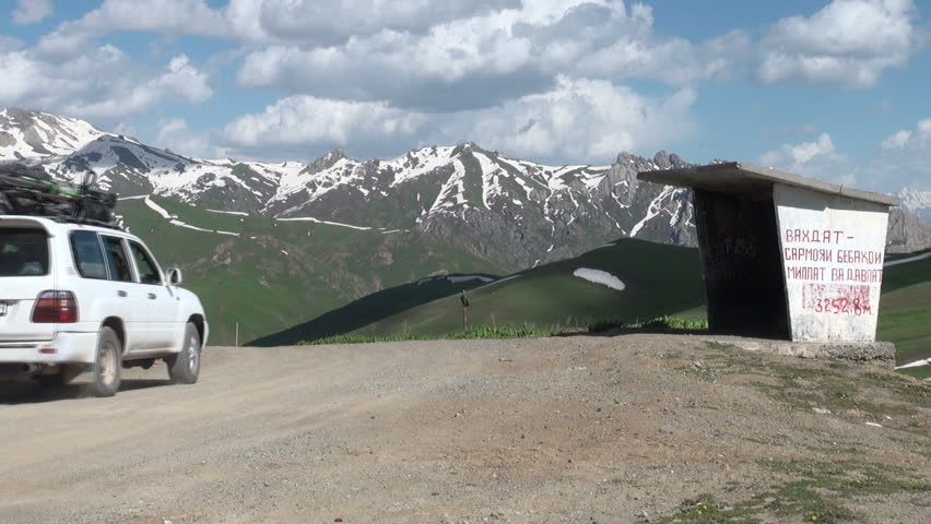 PAMIR, TAJIKISTAN: 18 JUNE 2013: A four wheel drive Landcruiser drives past an old Soviet bus station at a mountain pass in the Pamir ranges in Tajikistan - HD stock footage clip
