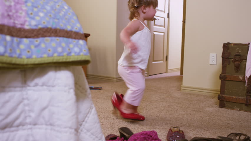 Cute young girl trying on mommy's shoes