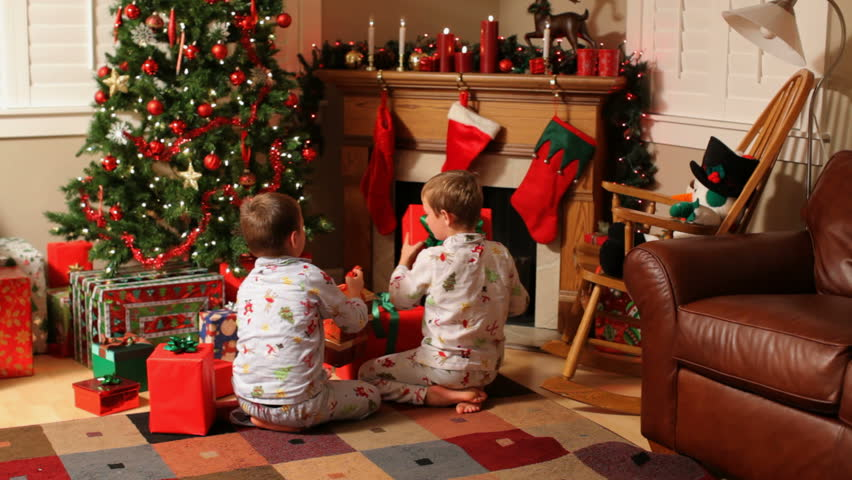 Two young boys run to gifts on Christmas morning