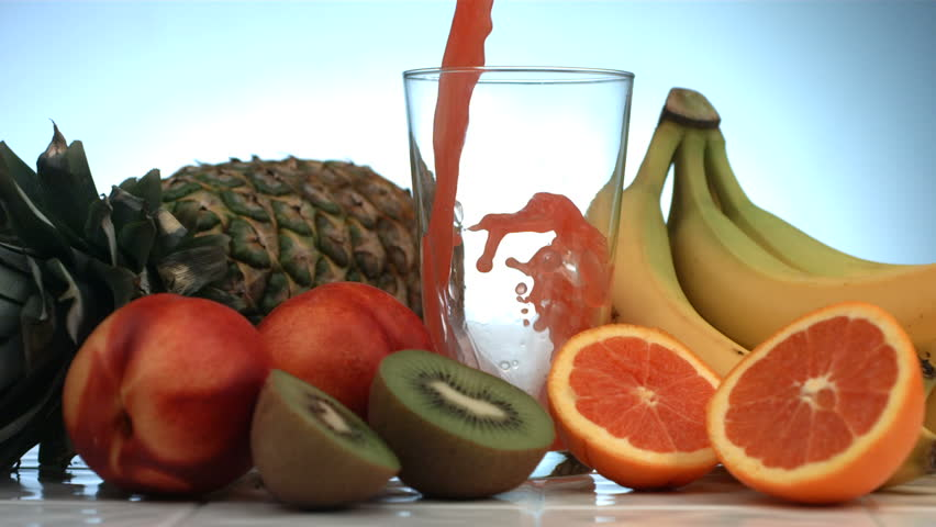 Fruit juice pouring into glass, slow motion