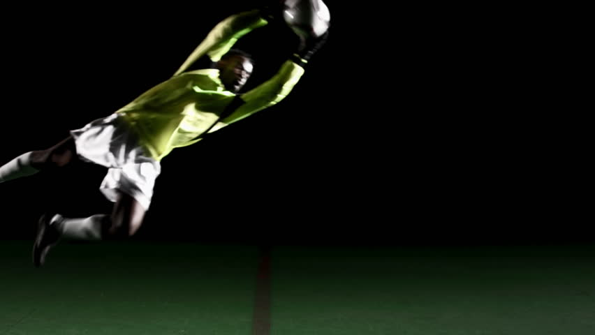 A soccer, or football, player goalie, goalkeeper that is dramatically and artistically lit, on an artificial field pitch on a black background, dives and stops a ball from scoring, wide shot - HD stock video clip