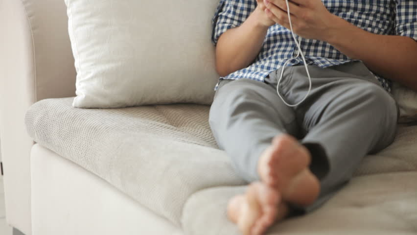 Attractive guy relaxing on sofa and listening to music with earphones - HD stock footage clip