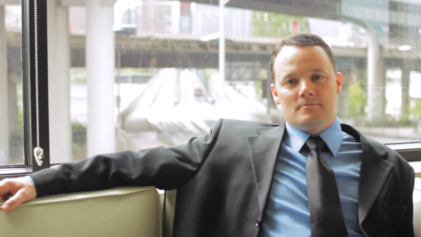 A businessman sits on a couch and looks at the camera with a blank expression. Medium shot - HD stock footage clip