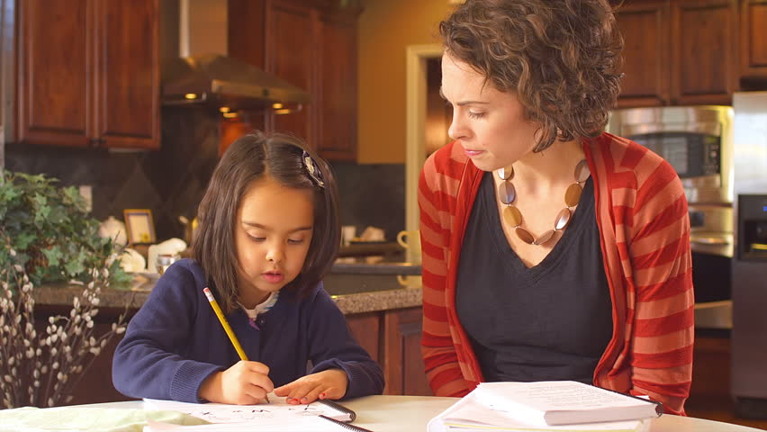 A mother sits at the kitchen table and assists her young daughter with her homework | Shutterstock HD Video #4637150