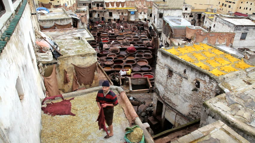 Morocco - April 2011: Local man lays out dyed textiles to dry on a house roof at a leather tannery in Fez, Morocco, in April 2011