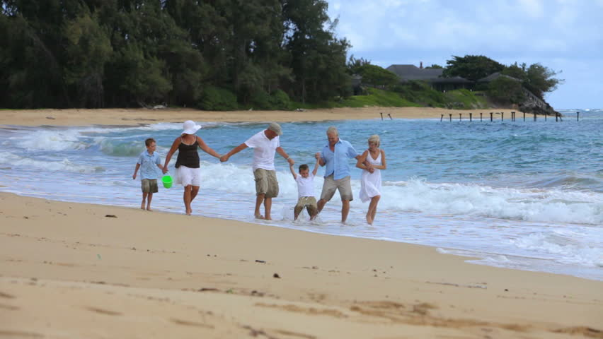 Multi-generation family walking together at beach