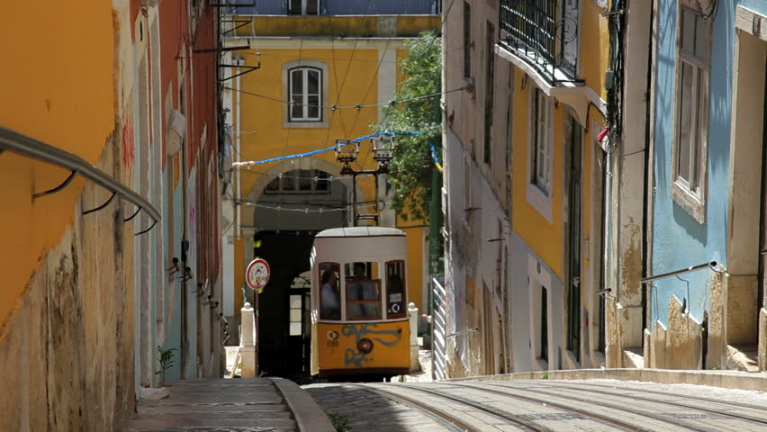 Portugal - June 2012: Trolley car driving up a narrow alleyway uphill past a short tunnel and a woman walking dogs in a residential neighborhood in Lisbon, Portugal in June, 2012