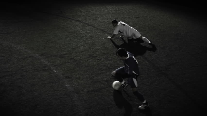A soccer player dribbles the ball through multiple defenders in slow motion