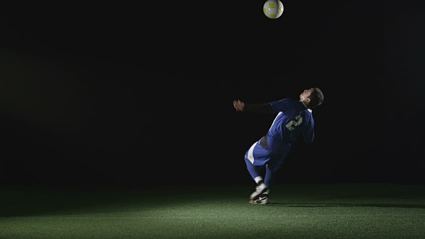 A very good soccer player catches a ball with his chest and then jumps in the air and kicks the ball. Wide slow motion shot.