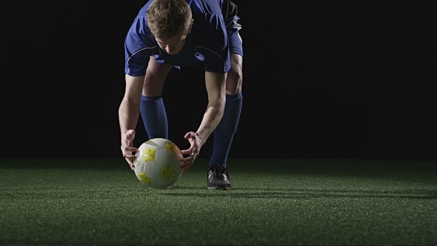 A soccer play sets up his free shot and takes a good kick at the ball. Medium slow motion shot.
