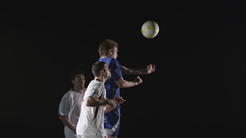 Three different soccer players jump in the air trying to head the soccer ball. Medium slow motion shot.