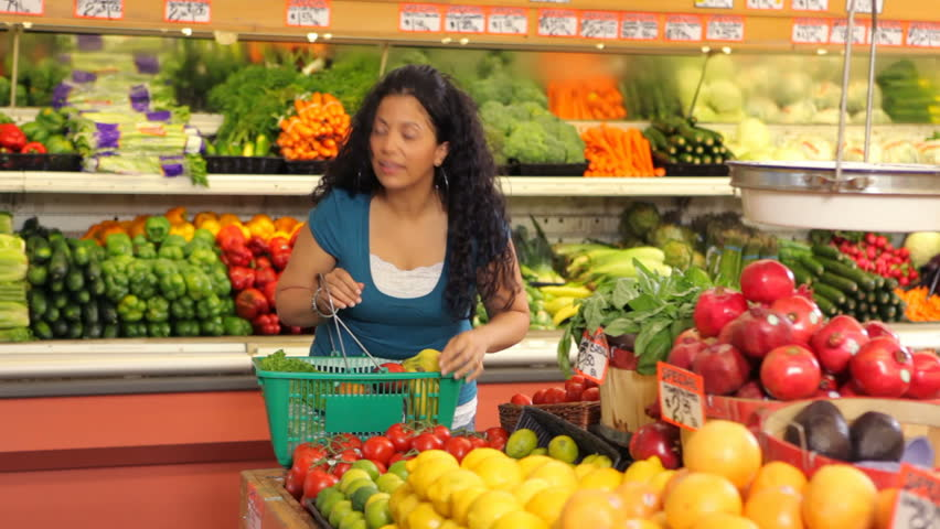 Grocery store worker helps woman shopping for produce