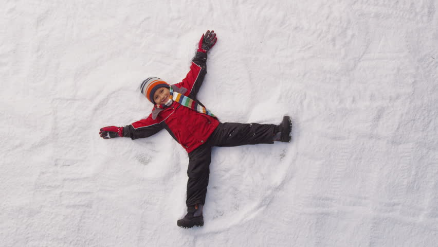 Young boy makes a snow angel. Overhead shot.
