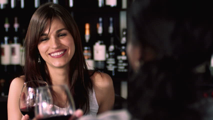 "Two pretty women sit drinking wine and saying ""Cheers!"" Medium shot. - HD stock video clip"