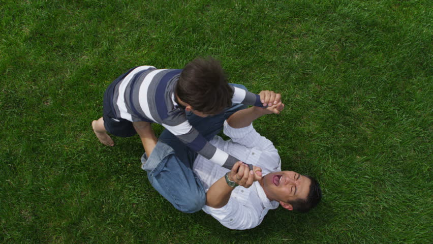 Father and son playing together in grass