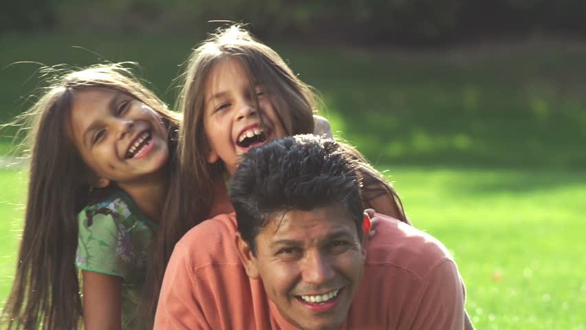 An adorable family pose for the camera. Medium shot.