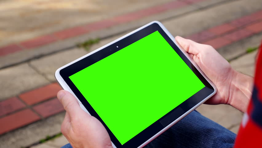A man holds a blank tablet PC in landscape orientation with a green screen for