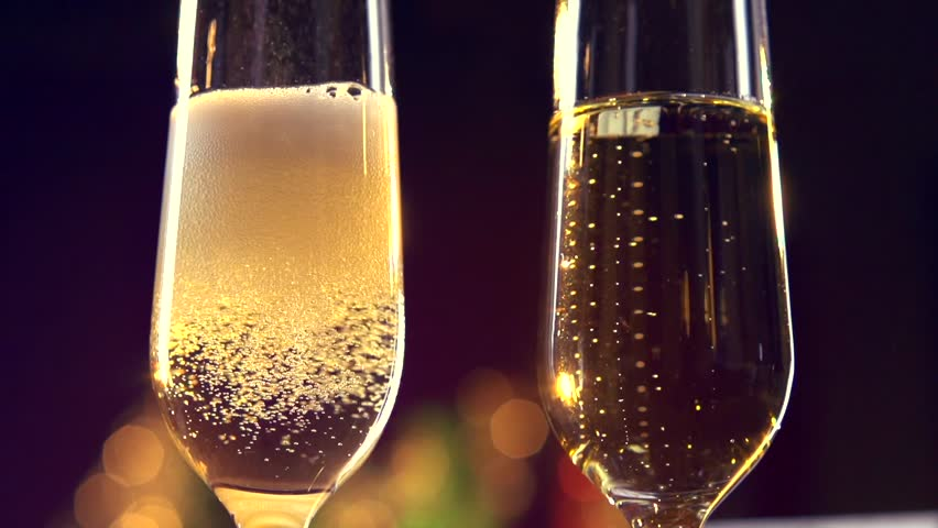 Champagne. Two Flutes with Sparkling Champagne over Holiday Bokeh Blinking Background.