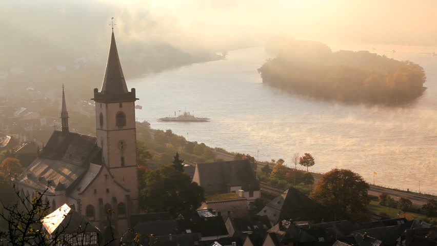 Ferry approaching a sleepy rural town with a prominent church tower on the Rhine River in the early morning mist Lorch, Rhine Valley, Germany - HD stock video clip