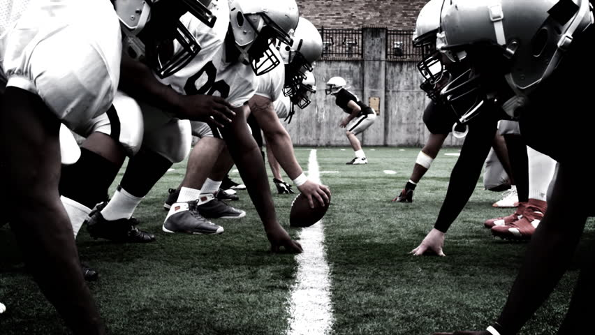 The defensive and offensive lines of two football teams meet at the line of scrimmage. High contrast, with camera flashes and time remap. | Shutterstock HD Video #4681844