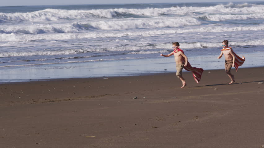 Two young boys running at beach with superhero costumes - HD stock footage clip