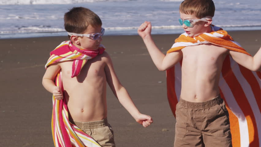 Young boys at beach flexing muscles with superhero costume