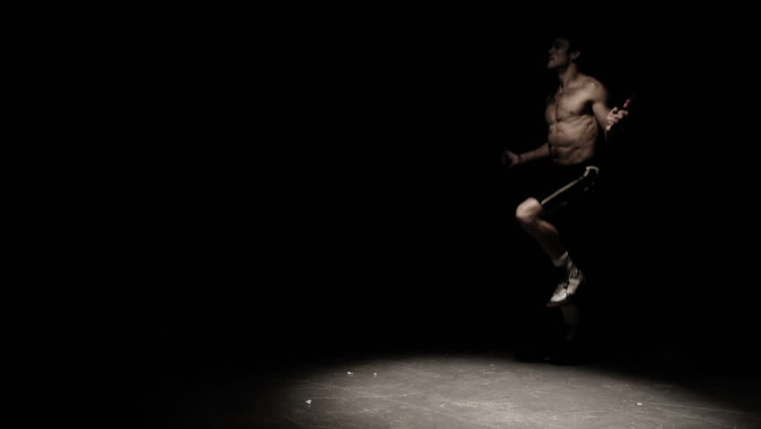 A fighter does some jump rope exercises in a dark room under a light - HD stock footage clip